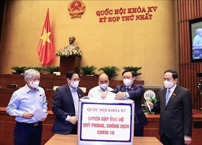 Chủ tịch nước Nguyễn Xuân Phúc, Thủ tướng Phạm Minh Chính, Chủ tịch Quốc hội Vương Đình Huệ và các đại biểu Quốc hội quyên góp ủng hộ Quỹ phòng chống dịch Covid-19. Ảnh: TTXVN