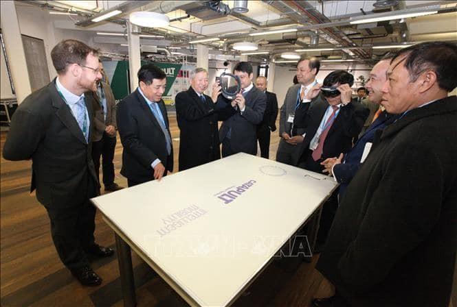 Bộ trưởng Nguyễn Chí Dũng và đoàn công tác xem giới thiệu về công nghệ thực tế ảo trong quy hoạch đô thị tại Trung tâm Đổi mới sáng tạo của Anh (NET). Ảnh: TTXVN
