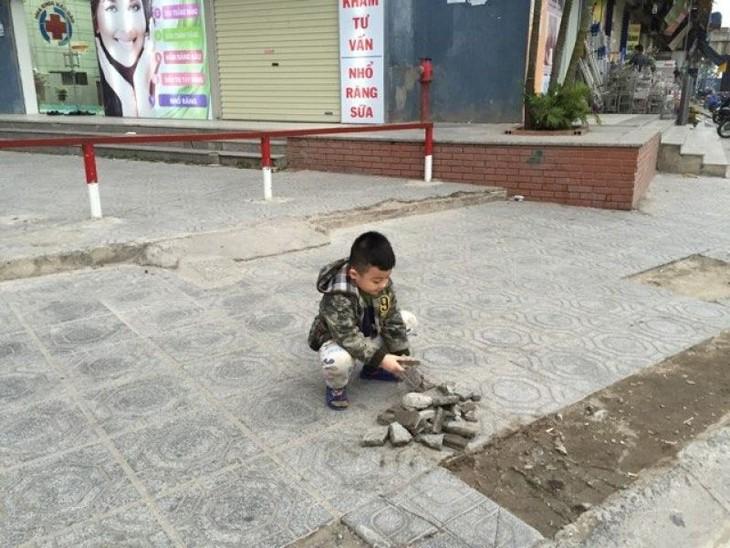 Trẻ em chơi mảnh gạch vỡ trên vỉa hè quanh khu dân cư.