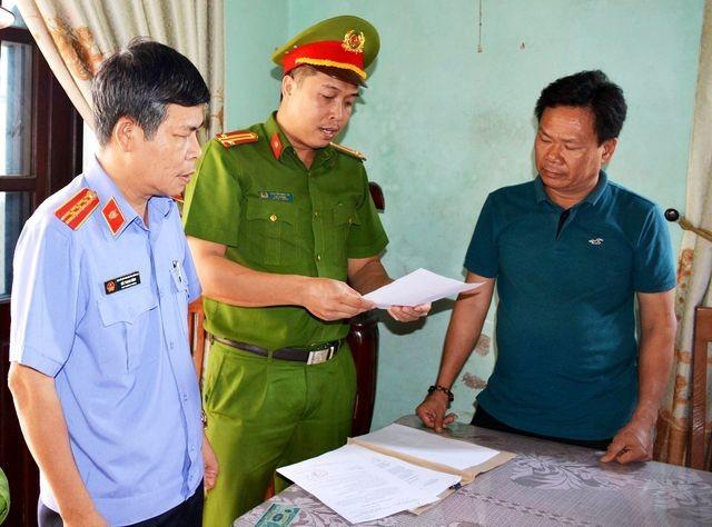 Lực lượng chức năng tống đạt các quyết định với đối tượng Lê Tự Trung. Ảnh CTV