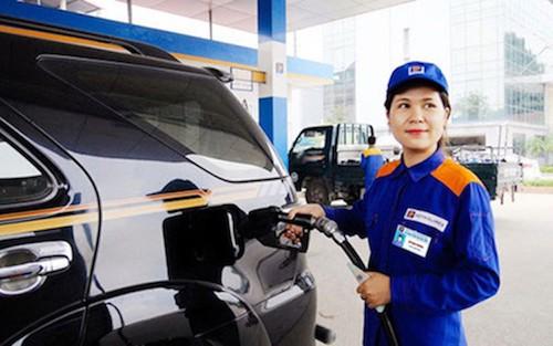 Nhân viên một cửa hàng xăng dầu của Petrolimex bơm nhiên liệu cho xe khách hàng.