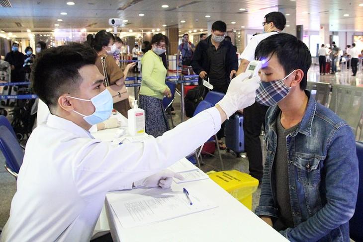 Nhân viên Trung tâm Kiểm dịch quốc tế đo thân nhiệt hành khách tại sân bay Tân Sơn Nhất.