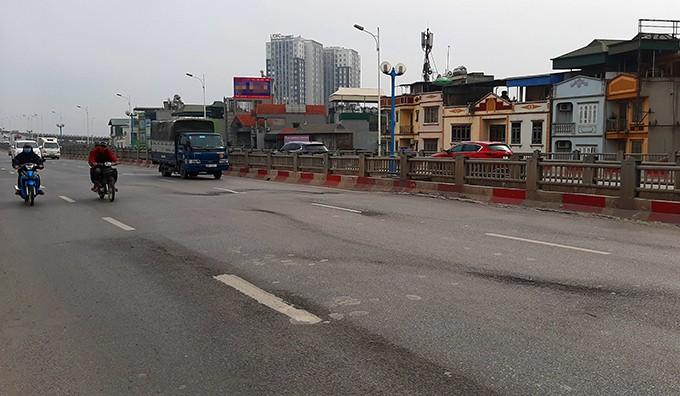 Mặt cầu Vĩnh Tuy đoạn gần đường Minh Khai bị xuống cấp, xuất hiện nhiều vệt lún, ổ gà.