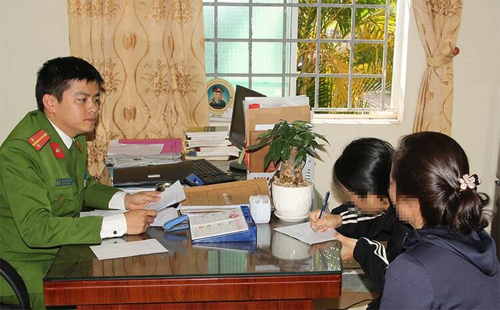 Nữ sinh (cầm bút bên phải) làm việc với cảnh sát dưới sự giám hộ của mẹ.