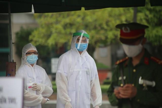 Hình ảnh các nhân viên y tế túc trực tại cổng Bệnh viện Bạch Mai để thực hiện kiểm tra y tế đối với người ra, vào
