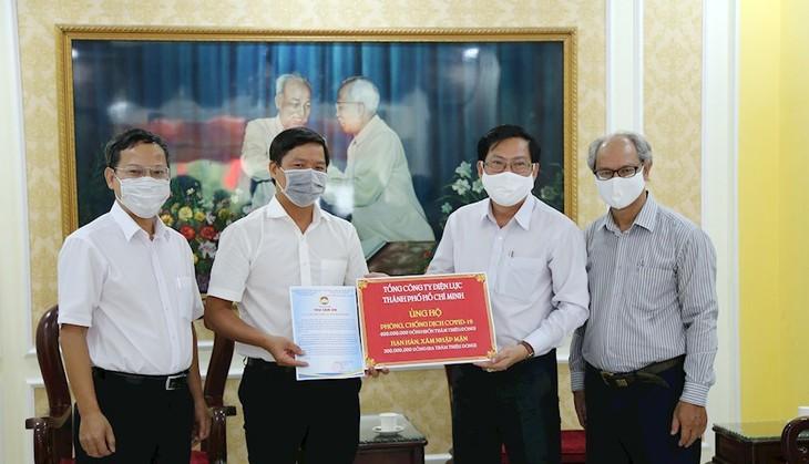 Ông Lê Văn Minh, Chủ tịch Công đoàn EVNHCMC trao ủng hộ 700 triệu đồng cho đại diện Ủy ban Mặt trận Tổ quốc Việt Nam TPHCM