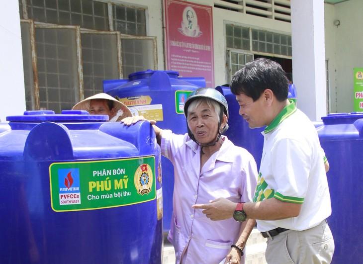 Ông Tống Xuân Phong, Chủ tịch Công đoàn PVFCCo trao tặng bồn chứa nước và các phần quà cho nhiều hộ gia đình chính sách.