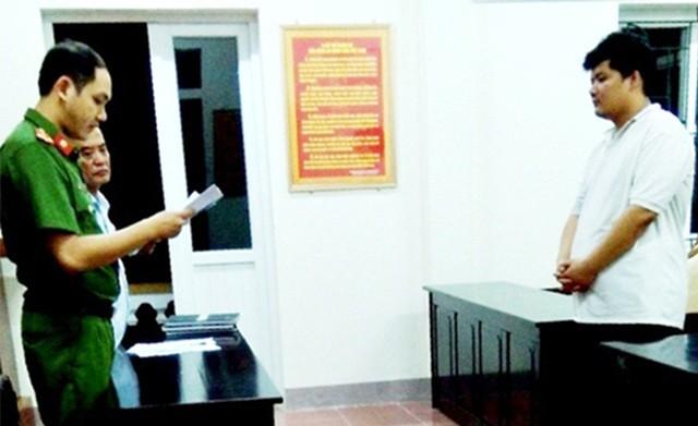 Nguyễn Mạnh Huấn nghe đại diện Cơ quan CSĐT Công an tỉnh Hà Tĩnh tống đạt quyết khởi tố vụ án.