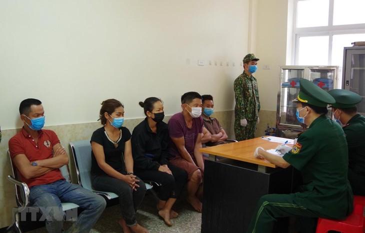 Cán bộ Biên phòng cửa khẩu Tân Thanh, Lạng Sơn lấy lời khai các đối tượng nhập cảnh trái phép ngày 1/8. Ảnh: TTXVN
