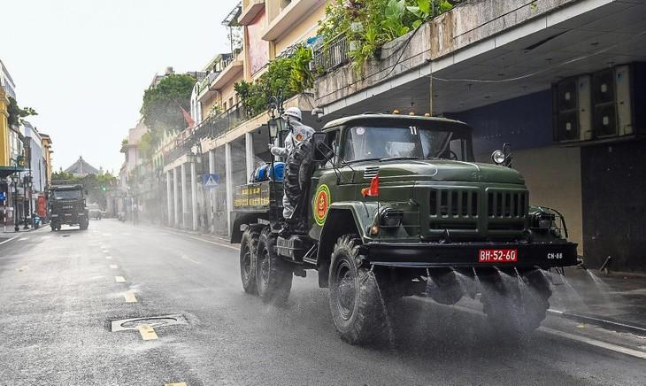 Quân đội phun khử khuẩn trên đường phố Hà Nội, sáng 26/7. Ảnh: Việt Linh