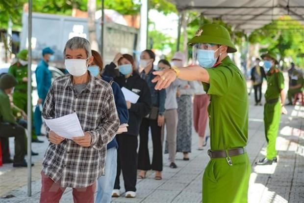 Hướng dẫn người tiêm thực hiện nghiêm việc phòng, chống dịch COVID-19 tại điểm tiêm Trung tâm Văn hóa quận Sơn Trà, Đà Nẵng. Ảnh: TTXVN