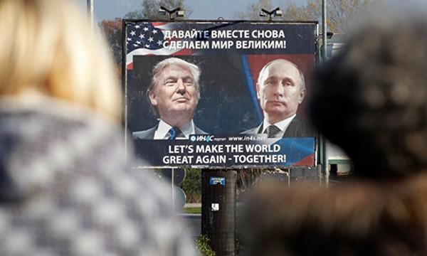"""Hai người đi bộ nhìn tấm áp phích có chân dung ông Putin và ông Trump với khẩu hiệu """"Hãy cùng khiến thế giới vĩ đại trở lại"""" tạiDanilovgrad, Montenegro, đông nam châu Âu. Ảnh:Sputnik"""