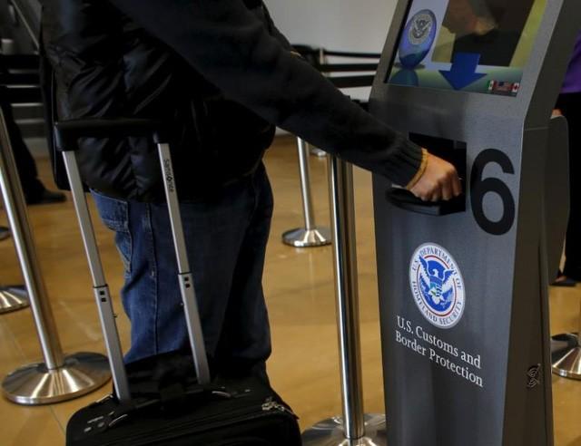 Khách du lịch quét hộ chiếu khi đi qua khu vực kiểm tra của Hải quan Mỹ (Ảnh: Reuters)