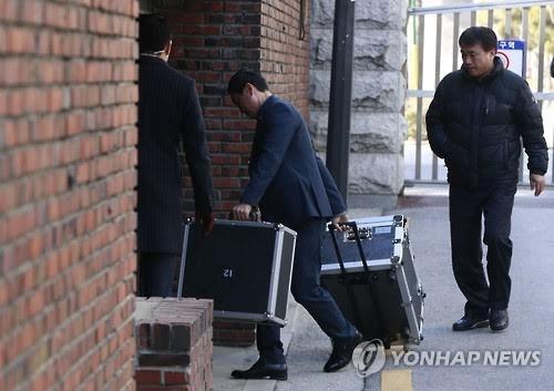 Nhân viên phủ tổng thống được cho là dỡ hành lý từ xe tải vào nhà riêng của Tổng thống bị phế truất Park Geun-hye. (Ảnh: Yonhap)