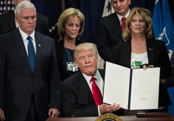 Tổng thống Donald Trump ký sắc lệnh bắt đầu kế hoạch xây tường biên giới với Mexico tại Bộ An ninh Nội địa ngày 25/1. Ảnh:AFP.