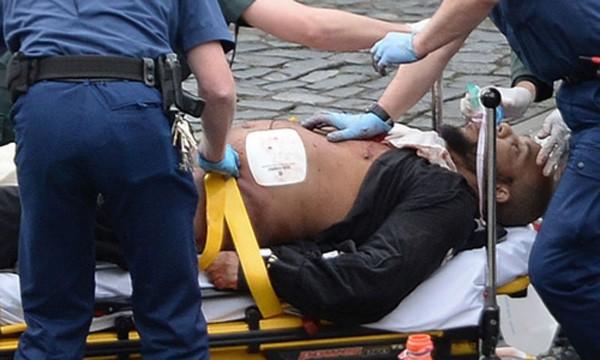 Khalid Masood được cấp cứu bên ngoài quốc hội trong khi cảnh sát có vũ trang đứng canh. Ảnh:PA