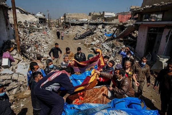 Cư dân quận al-Jadida thu gom các thi thể sau vụ không kích. Ảnh:Iraq News.
