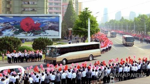 Người dân Triều Tiên vẫy cờ, hoa chào đón các nhà khoa học tên lửa được mời về thủ đô Bình Nhưỡng hôm 18/5 (Ảnh: KCNA)