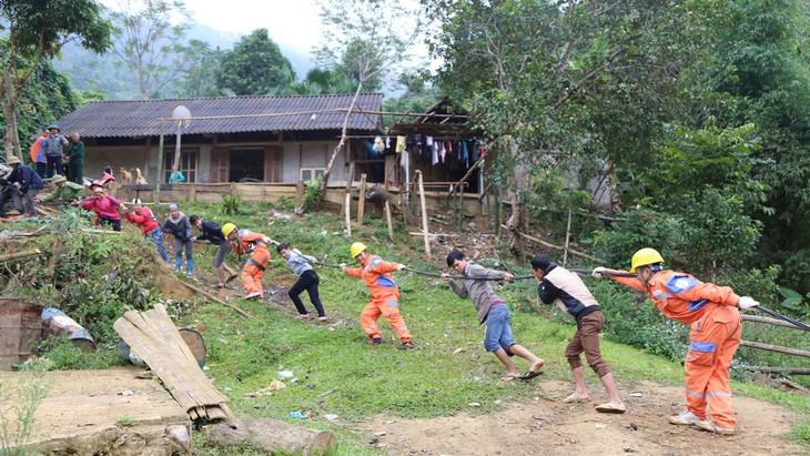 Bà con dân tộc thôn Đá Đen cùng cán bộ nhân viên Điện lực Văn Chấn kéo dây để đưa điện về thôn
