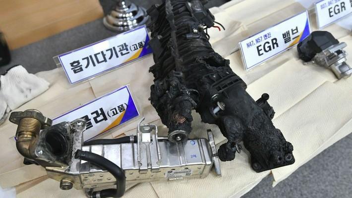 Một số bộ phận của một chiếc xe BMW tự bốc cháy được nhà chức trách Hàn Quốc đưa ra trước báo giới trong một cuộc họp báo ngày 24/12 ở Seoul - Ảnh: Getty/Bloomberg.
