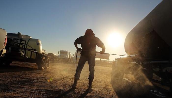 Một công nhân đang rửa những chiếc xe chở dầu tại một mỏ dầu ở Texas, Mỹ - Ảnh:Getty/CNBC.