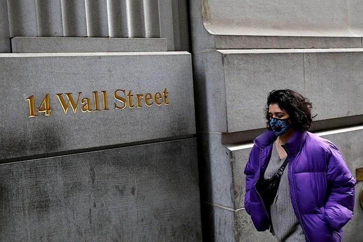 Một người đeo khẩu trang đi bộ dọc theo phố Wall, New York.Ảnh: Reuters