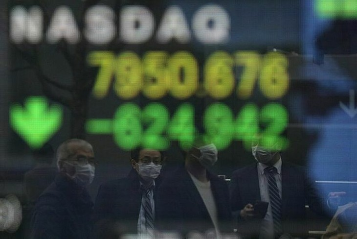 Người dân đi qua bảng điện tử của một công ty chứng khoán tại Nhật Bản. Ảnh:Reuters