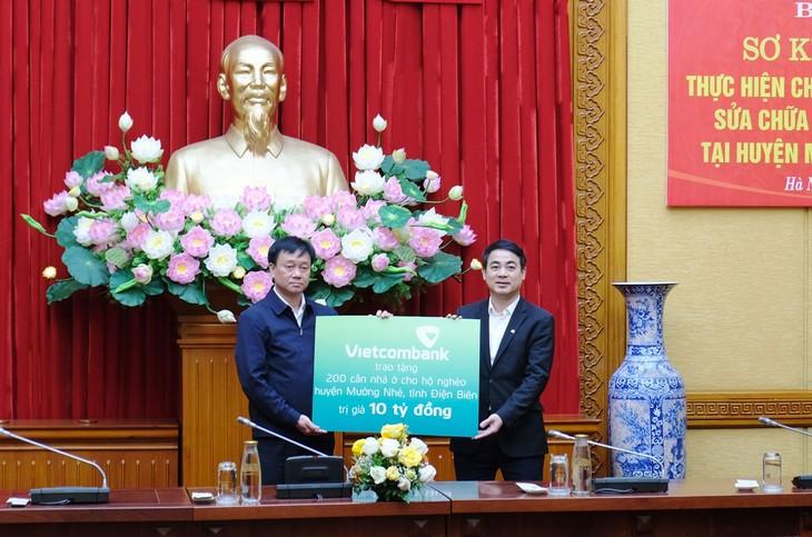 Chủ tịch HĐQT Ngân hàng TMCP Ngoại thương Việt Nam Nghiêm Xuân Thành (bên phải) trao biển tượng trưng 10 tỷ đồng hỗ trợ xây dựng, sửa chữa nhà cho 200 hộ nghèo tại huyện Mường Nhé, tỉnh Điện Biên