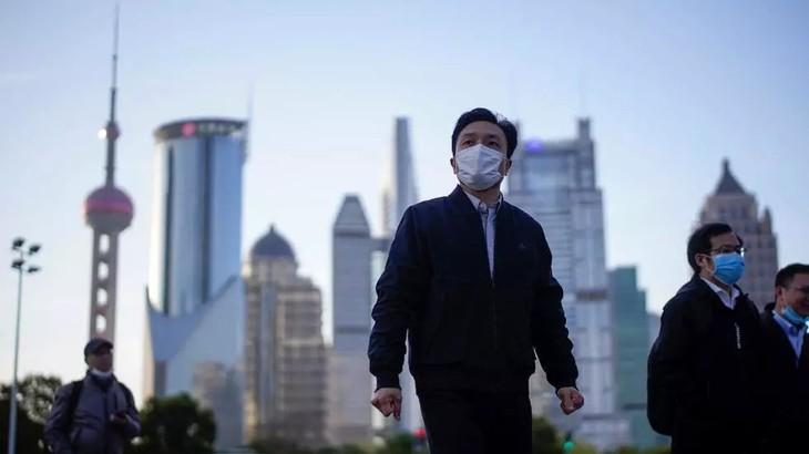 Người dân Trung Quốc đeo khẩu trang tại khu tài chính Lujiazui ở Thượng Hải ngày 19/3.Ảnh: Reuters