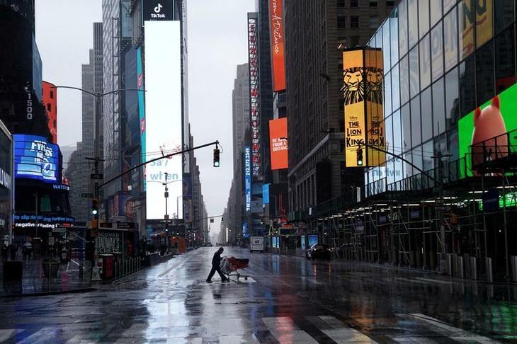 Một người vô gia cư sang đường tại Quảng trường Thời đại vắng vẻ ở New York (Mỹ). Ảnh:Reuters