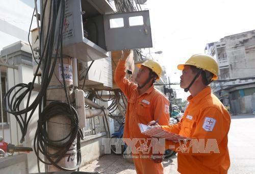 Nhân viên điện lực ghi chỉ số tiêu thụ điện. Ảnh: TTXVN