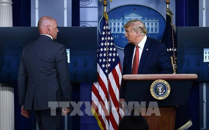 Mật vụ Mỹ hộ tống Tổng thống Donald Trump (phải) rời khỏi buổi họp báo tại Nhà Trắng khi xảy ra vụ nổ súng, ngày 10/8/2020. Ảnh: AFP/TTXVN