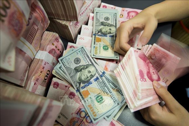 Kiểm đồng 100 Nhân dân tệ tại ngân hàng ở tỉnh Giang Tô, Trung Quốc. Ảnh: AFP/TTXVN