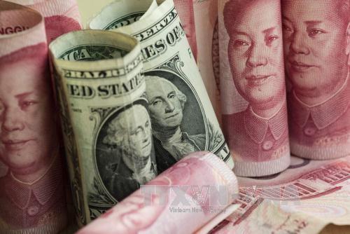 Tại các ngân hàng thương mại, sáng nay, giá đồng Nhân dân tệ (NDT) tăng trong khi giá đồng USD không đổi. Ảnh minh hoạ: AFP/TTXVN