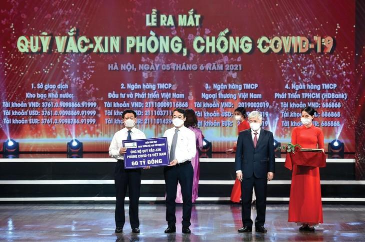 Ông Nghiêm Xuân Thành, Bí thư Đảng ủy, Chủ tịch HĐQT Vietcombank (thứ 2 từ trái sang) trao biển ủng hộ 60 tỷ đồng cho Quỹ Vắc-xin phòng, chống Covid-19