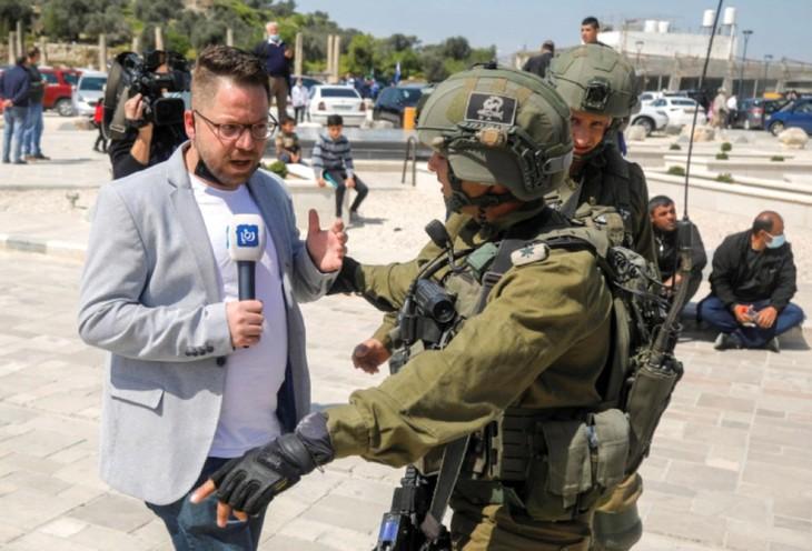 Một phóng viên truyền hình đối diện quân lính Israel tại khu vực Bờ Tây vào tháng 3/2021